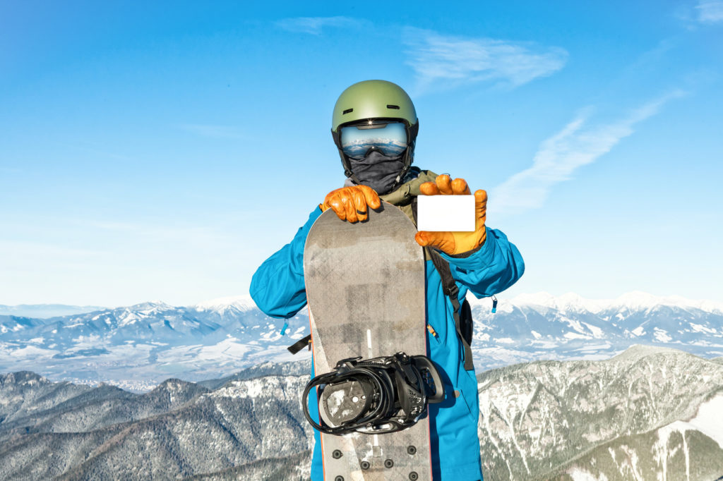Snowboarder holding blank ski-pass with mountains on background